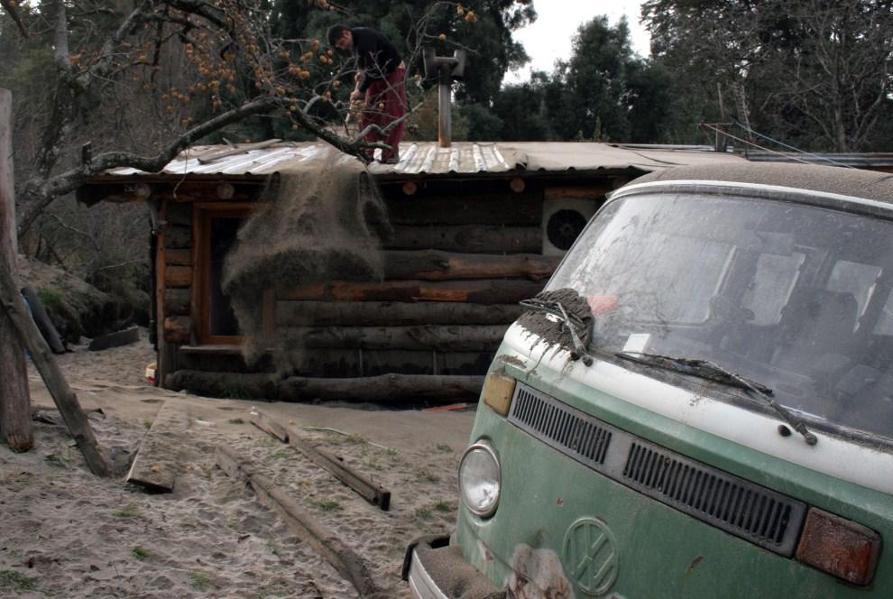 14. CHILE, Puyehue, 6 czerwca 2011: Mężczyzna zgarnia pył wulkaniczny z dachu domu. AFP PHOTO/FRANCISCO RAMOS MEJIA