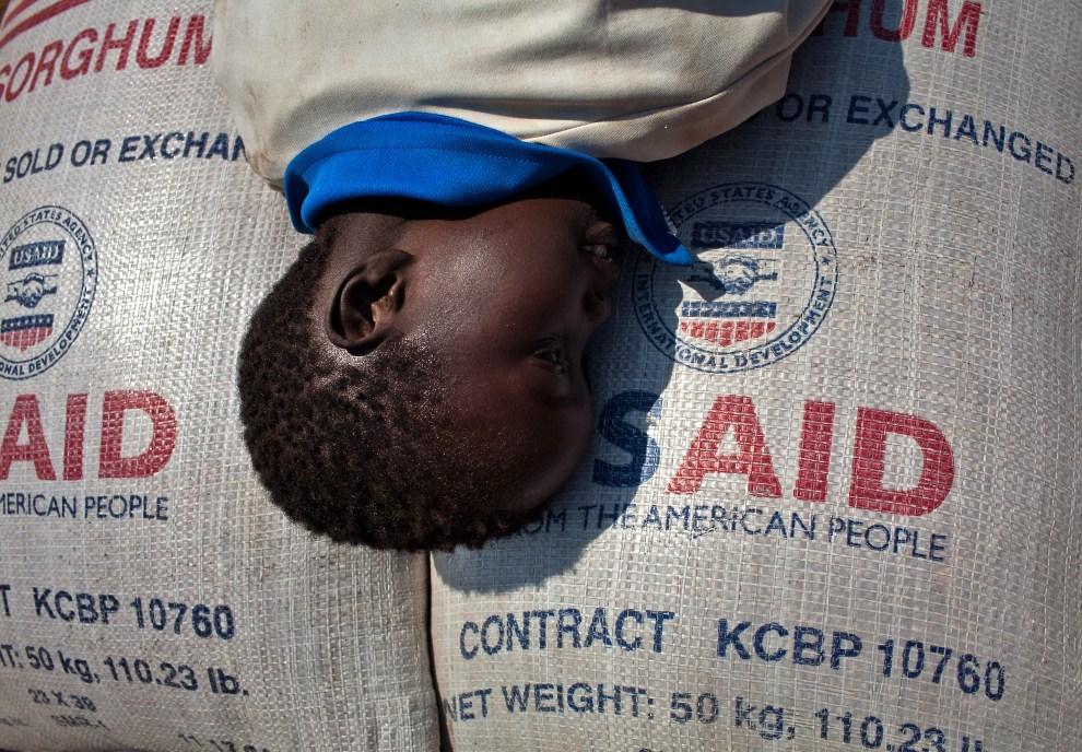 15. SUDAN, Dżuba, 6 stycznia 2011: Dziecko odpoczywające na workach z żywnością wysyłaną do Sudanu w ramach pomocy międzynarodowej. AFP PHOTO/YASUYOSHI CHIBA