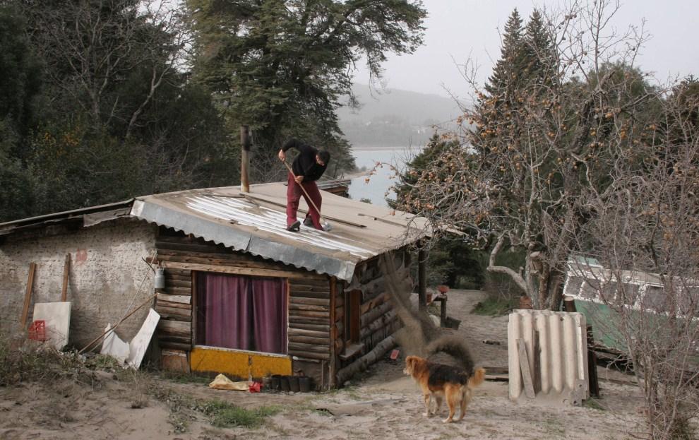 15. CHILE, Puyehue, 6 czerwca 2011: Mężczyzna zgarnia pył wulkaniczny z dachu domu. AFP PHOTO/FRANCISCO RAMOS MEJIA