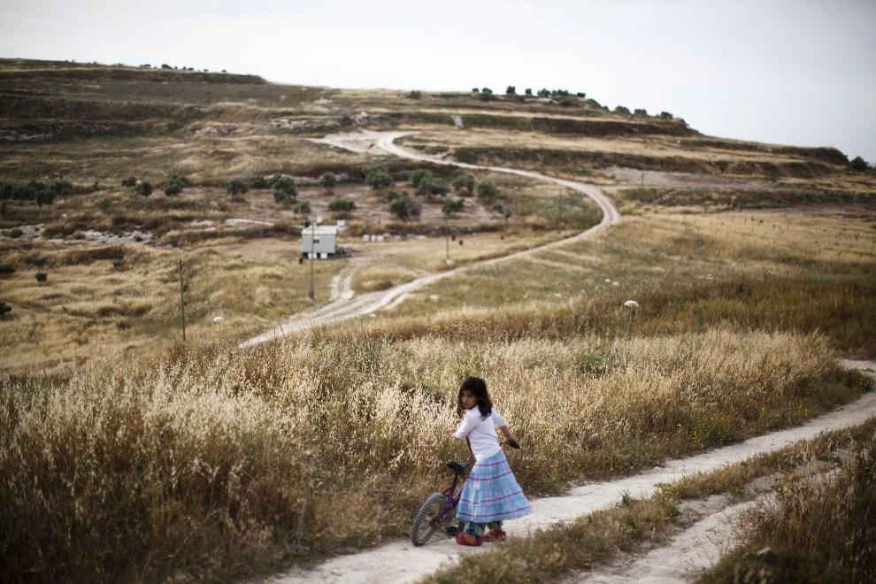18. ZACHODNI BRZEG, Havat Gilad, 24 maja 2011: Córka osadników bawi się na wzgórzach wokół Havat Gilad. (Foto: Uriel Sinai/Getty Images)