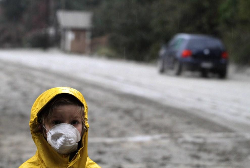 18. ARGENTYNA, Bariloche, 7 czerwca 2011: Chłopiec w masce na zasypanej przez pył wulkaniczny drodze. AFP PHOTO/FRANCISCO RAMOS MEJIA