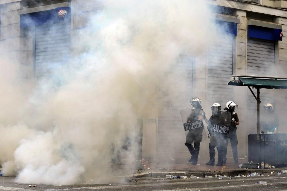 19. GRECJA, Ateny, 15 czerwca 2011: Policjanci w chmurze gazu łzawiącego. AFP PHOTO / ARIS MESSINIS