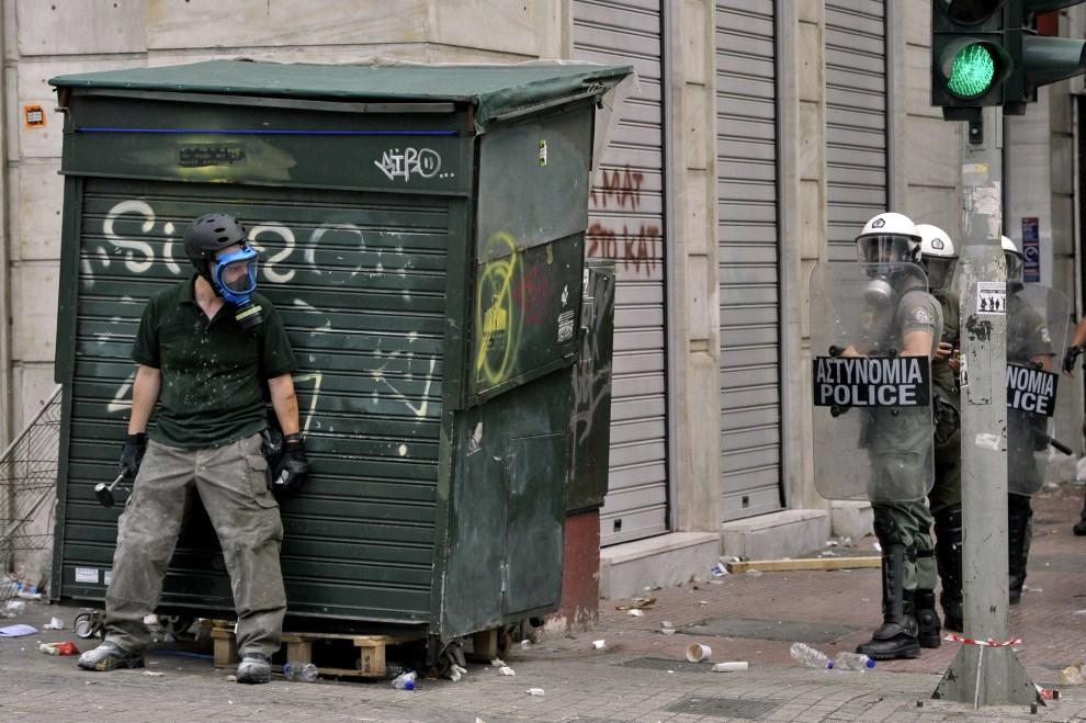 1. GREACJA, Ateny, 15 czerwca 2011: Protestujący ukrywa się przed policjantami podczas demonstracji w stolicy Grecji. AFP PHOTO / ARIS MESSINIS