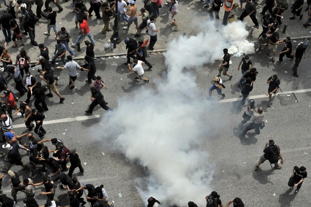 20. GRECJA, Ateny, 15 czerwca 2011: Rozbiegający się tłum po wrzuceniu granatu z gazem łzawiącym. AFP PHOTO / Aris Messinis