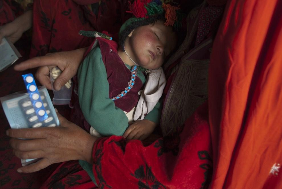 20. AFGANISTAN, Gharmboloq, 12 czerwca 2011: Dziecko śpiące w ramionach matki, która odbiera lekarstwa przywiezione przez pracowników mobilnej przychodni. (Foto: Paula   Bronstein/Getty Images)