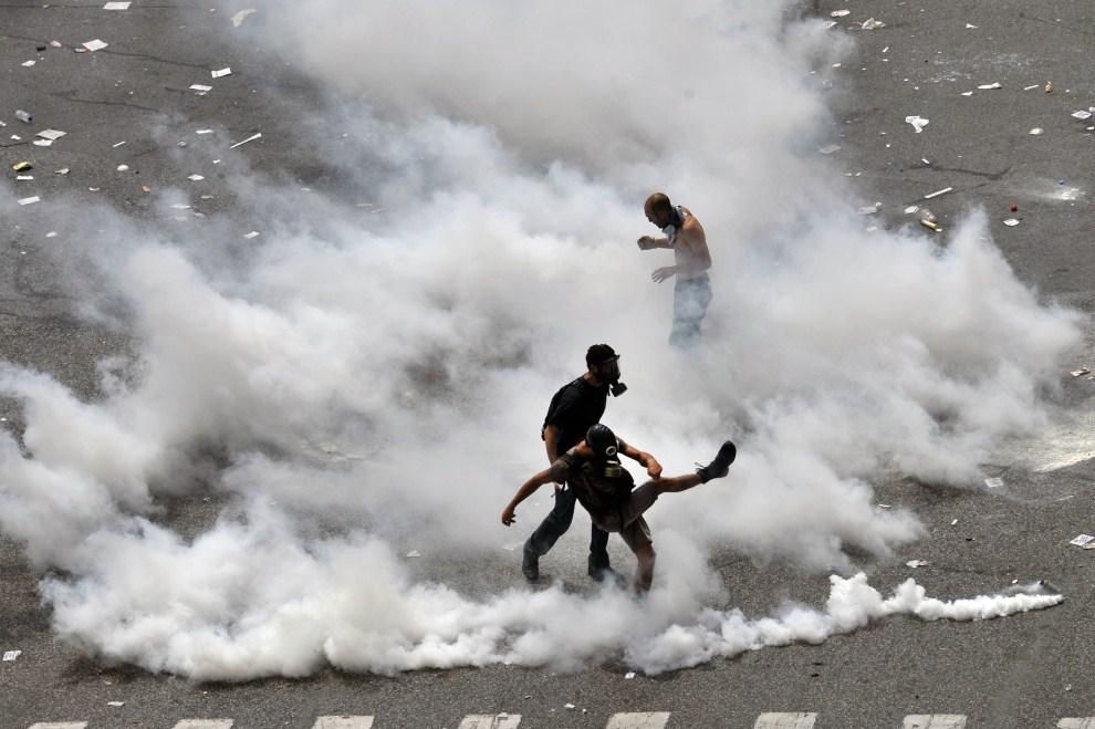 21. GRECJA, Ateny, 15 czerwca 2011: Protestujący odrzucają pojemniki z gazem łzawiącym. AFP PHOTO / Aris Messinis