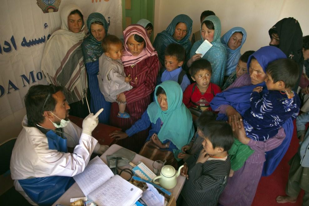21. AFGANISTAN, Raquol, 9 czerwca 2011: Lekarz rozmawia z pacjentami mobilnej przychodni. (Foto: Paula Bronstein/Getty Images)