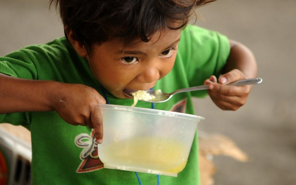 22. FILIPINY, Manila, 20 maja 2011: Bezdomny chłopiec je zupę wydawaną przez organizacje katolickie. AFP PHOTO/NOEL CELIS
