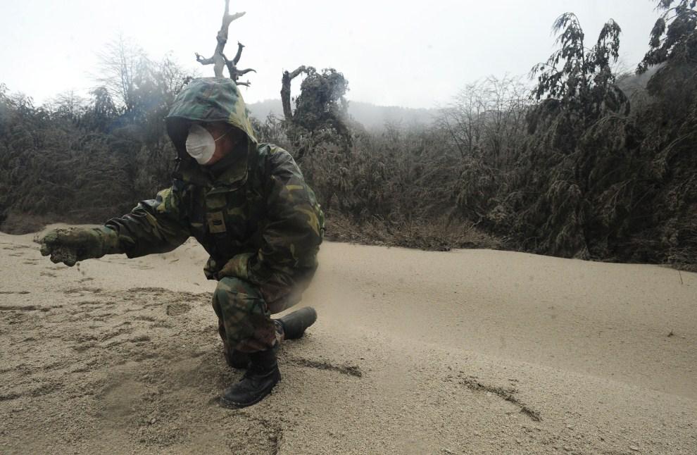 22. CHILE, Puyehue, 7 czerwca 2011: Żołnierz uczestniczący w akcji ratowniczej przygląda się pyłowi wulkanicznemu. AFP PHOTO/CLAUDIO SANTANA