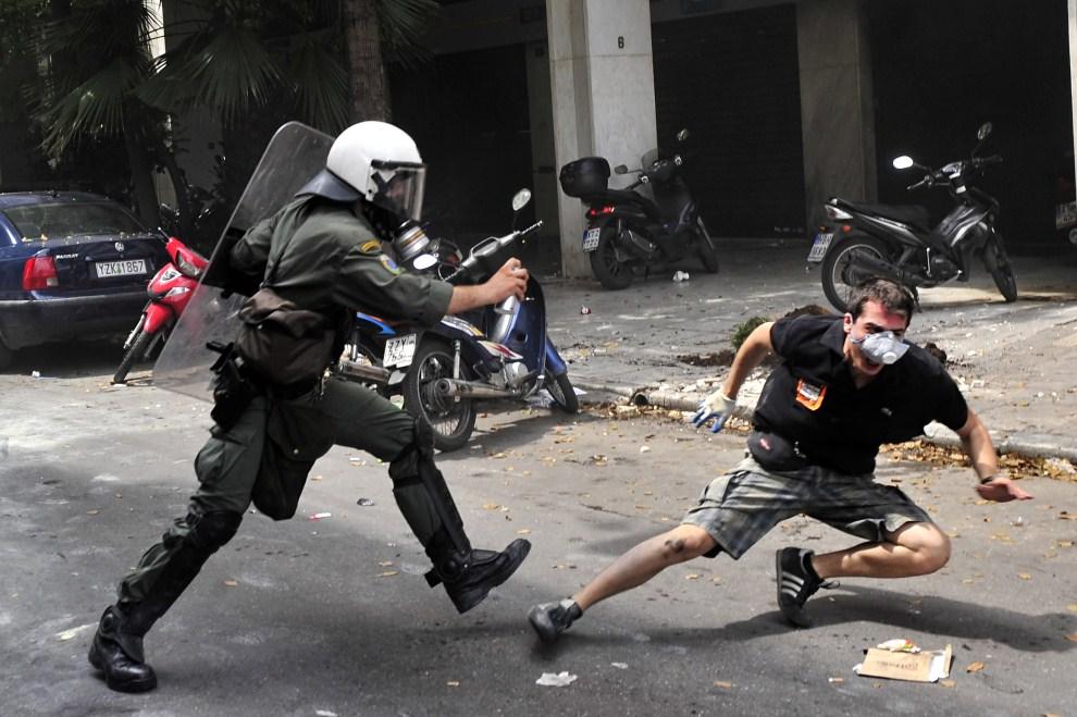 24. GRECJA, Ateny, 15 czerwca 2011: Protestujący mężczyzna stara się uciec policjantowi. AFP PHOTO / LOUISA GOULIAMAKI