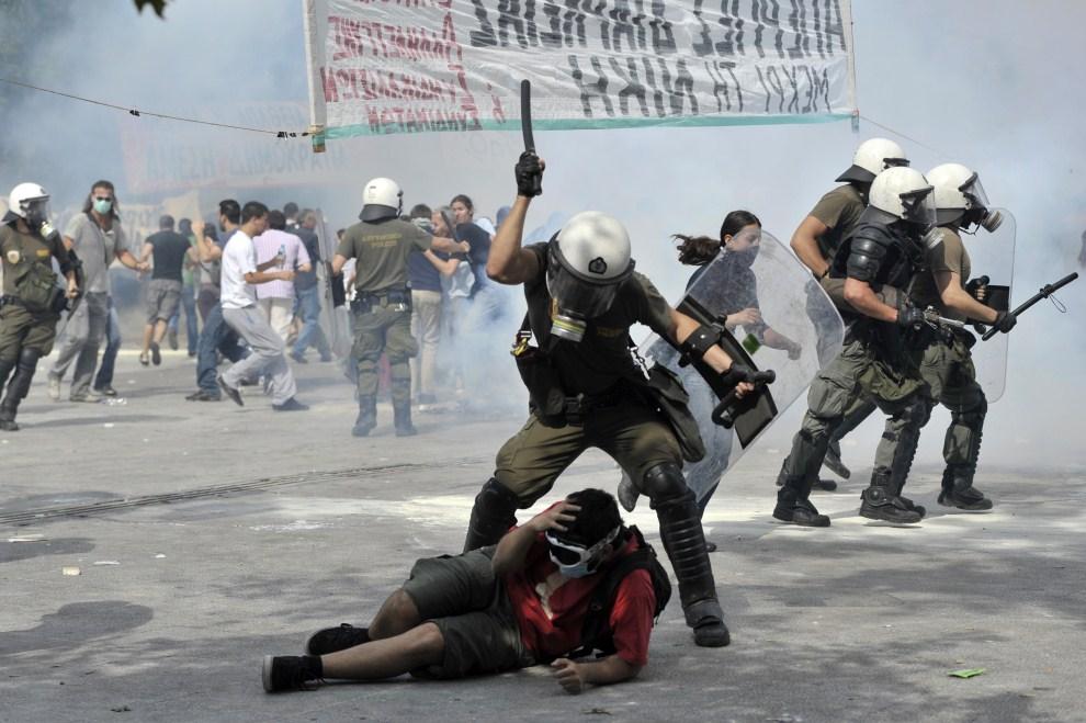 25. GRECJA, Ateny, 15 czerwca 2011: Protestujący atakowany przez policjanta. AFP PHOTO / ARIS MESSINIS