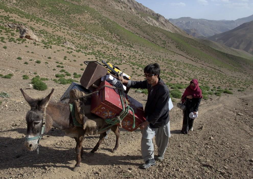 25. AFGANISTAN, Raquol, 9 czerwca 2011: Jawad Ahmadi w towarzystwie akuszerki  Raqaiu Khosnod wędrują przełęczą w pobliżu Raquol. (Foto: Paula Bronstein/Getty Images)