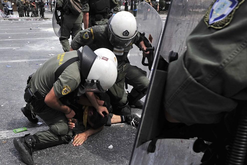 26. GRECJA, Ateny, 15 czerwca 2011: Policjanci zatrzymują uczestnika protestów. AFP PHOTO / LOUISA GOULIAMAKI
