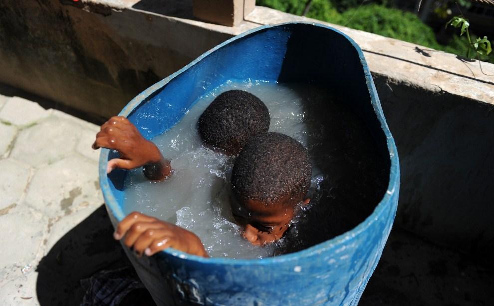 27. BRAZYLIA, Rio de Janeiro, 24 stycznia 2011: Dzieci z faweli chłodzą się w beczce z wodą. AFP PHOTO/VANDERLEI ALMEIDA