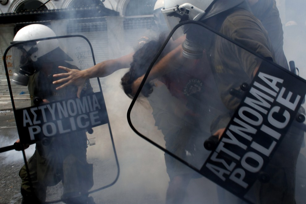 27. GRECJA, Ateny, 15 czerwca 2011: Policjanci zatrzymują uczestników protestów. AFP PHOTO / ANGELOS TZORTZINIS