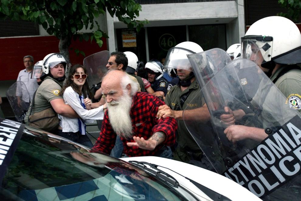 28. GRECJA, Ateny, 15 czerwca 2011: Policjanci zatrzymują uczestnika protestów. AFP PHOTO / Panagiotis Tzamaros
