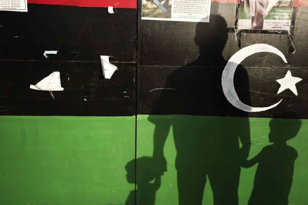 2. LIBIA, Bengazi, 11 czerwca 2011: Cień ojca z dwiema córkami rzucany na jedną ze ścian przy Placu Rewolucji. AFP PHOTO/GIANLUIGI GUERCIA
