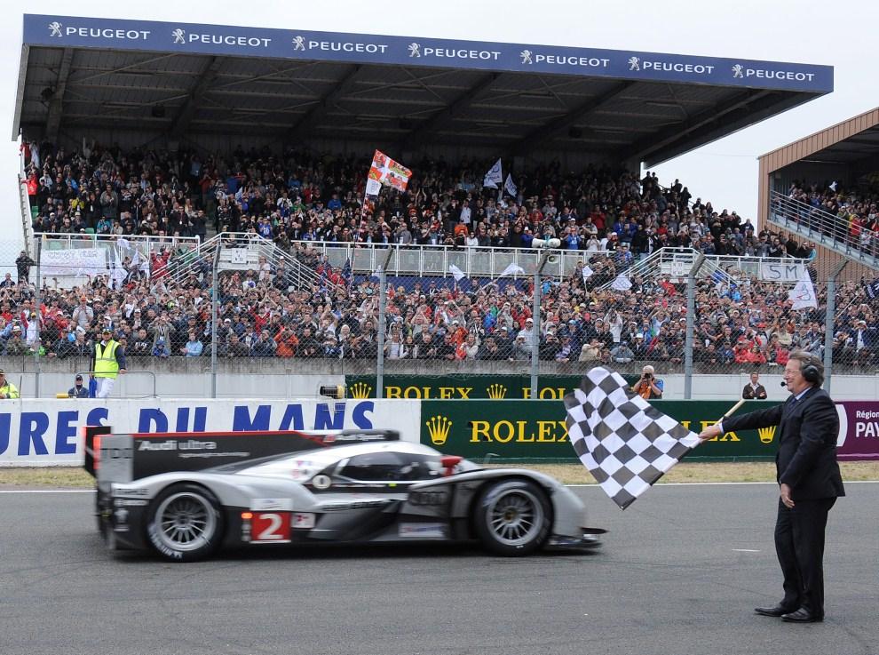 32. FRANCJA, Le Mans, 12 czerwca 2011: Dyrektor wyścigu - Daniel Poissenot – macha flagą przed zwycięskim samochodem wyścigu. AFP PHOTO / JEAN-FRANCOIS MONIER
