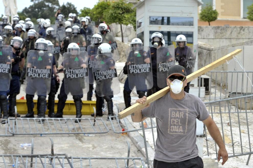 4. GRECJA, Ateny, 15 czerwca 2011: Mężczyzna uzbrojony w drąg na tle policjantów. AFP PHOTO / Aris Messinis