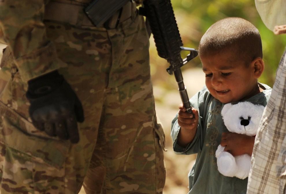 6. AFGANISTAN, Tarok Kolache, 1 kwietnia 2010: Afgańskie dziecko bawi się lufą karabinu M-16. AFP PHOTO/Peter PARKS