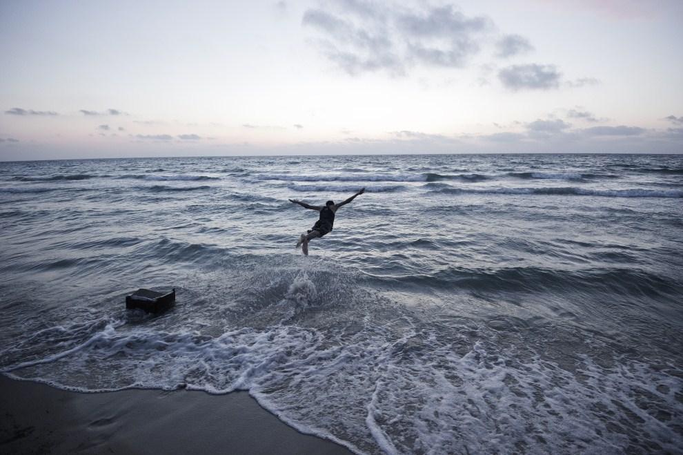 7. LIBIA, Bengazi, 12 czerwca 2011: Młody Libijczyk skacze do morza w pobliżu Bengazi. AFP PHOTO/GIANLUIGI GUERCIA
