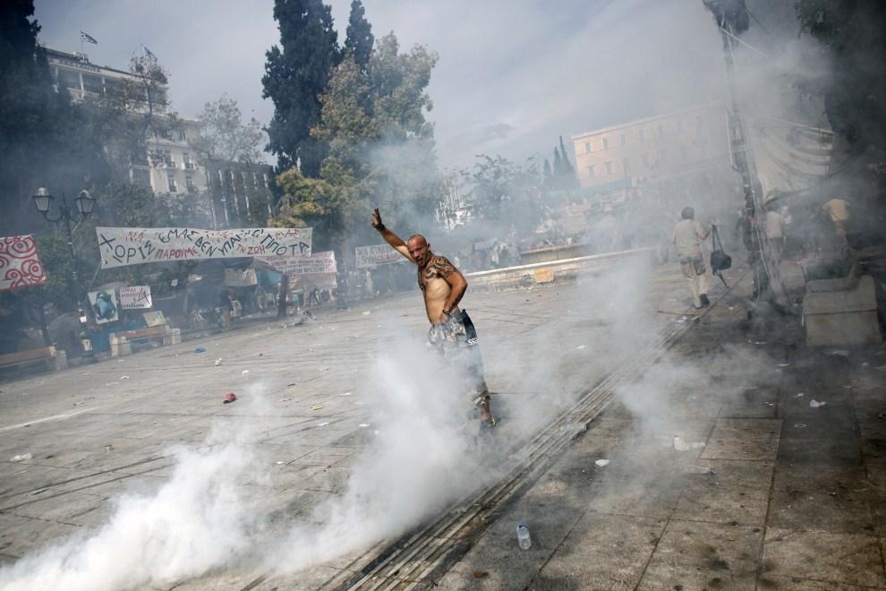 7. GRECJA, Ateny, 15 czerwca 2011: Mężczyzna stara się złapać oddech po tym, jak wszedł w chmurę gazu łzawiącego. AFP PHOTO / Angelos Tzortzinis