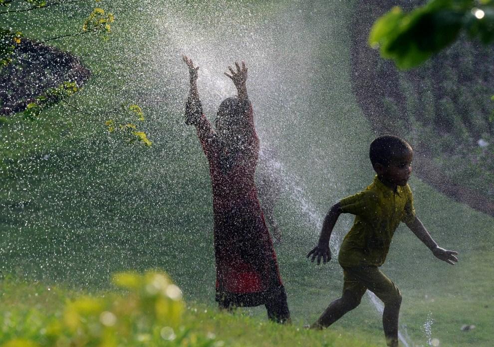 8. PAKISTAN, Lahore, 14 czerwca 2011: Dzieci bawiące się pomiędzy zraszaczami. AFP PHOTO/ARIF ALI