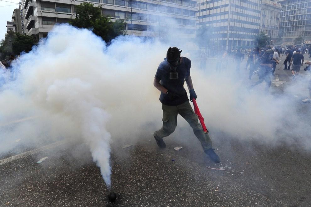 9. GRECJA, Ateny, 15 czerwca 2011: Mężczyzna biegnie obok granatu z gazem łzawiącym. AFP PHOTO / Aris Messinis