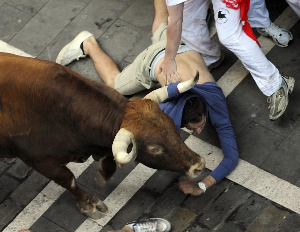 12. HISZPANIA, Pampeluna, 8 lipca 2011: Mężczyzna zaczepiony rogiem pędzącego byka. AFP PHOTO / ANDER GILLENEA