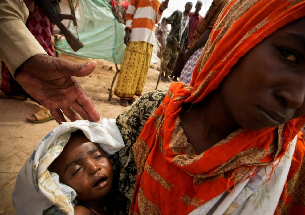 14. SOMALIA, Mogadiszu, 15 lipca 2011: Somalijka z dzieckiem mieszkająca w obozie dla uchodźców w Mogadiszu. AFP PHOTO / AU-UN IST / STUART PRICE