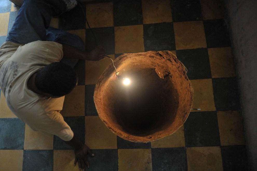 15. GWATEMALA, Guatemala City, 19 lipca 2011: Mężczyzna przygląda się dziurze jaka powstała pod posadzkę jego domu. AFP PHOTO / Johan ORDONEZ