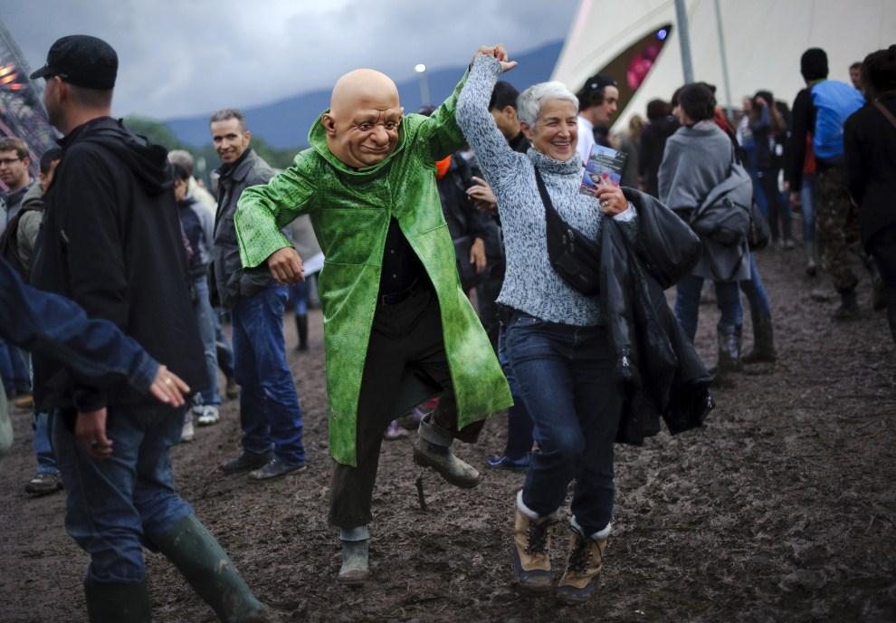 """17. SZWAJCARIA, Nyon, 20 lipca 2011: Kobieta tańczy z jednym z aktów """"Les Homs Fums"""". AFP PHOTO / FABRICE COFFRINI"""