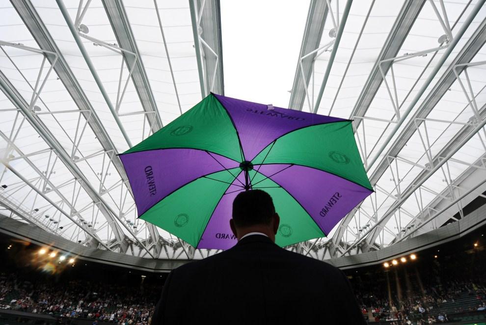 18. WIELKA BRYTANIA, Londyn, 20 czerwca 2011: Sędzia chroni się przed deszczem na centralnym korcie. AFP PHOTO/CARL DE SOUZA