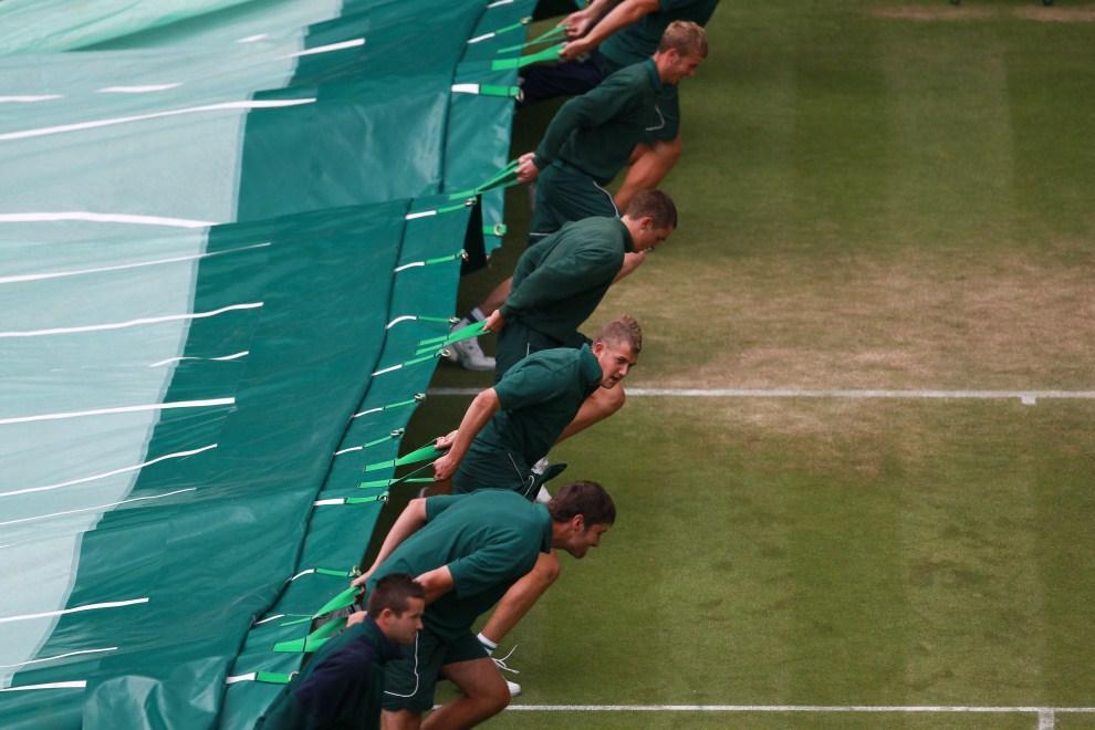 19. WIELKA BRYTANIA, Londyn, 24 czerwca 2011: Pracownicy techniczni przykrywają kort podczas opadów deszczu. (Foto: Julian Finney/Getty Images)
