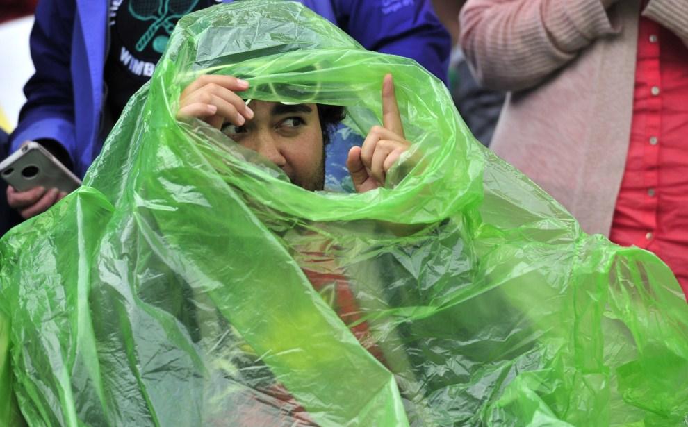 20. WIELKA BRYTANIA, Londyn, 20 czerwca 2011: Kibic w pelerynie chroni się przed deszczem. AFP PHOTO /GLYN KIRK