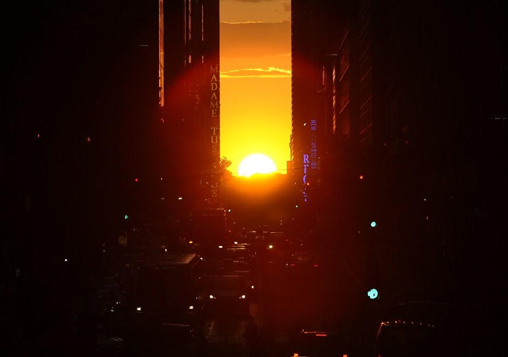 """22. USA, New York, 13 lipca 2011: """"Manhattanhenge"""", czyli obserwowane dwa razy do roku zjawisko, kiedy zachodzące słońce idealnie równa się z kierunkiem zachodnich i wschodnich ulic Manhattanu. AFP PHOTO / TIMOTHY A. CLARY"""