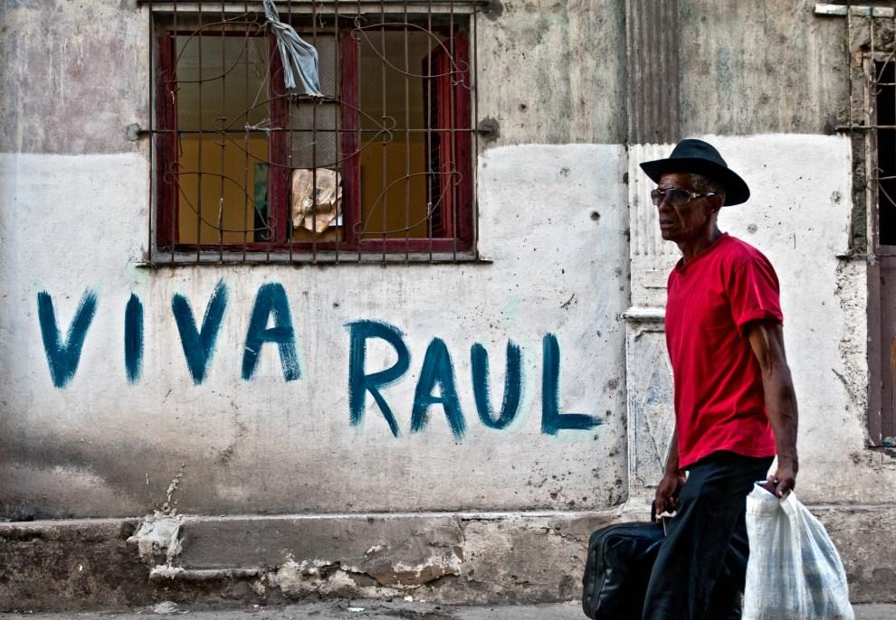 23. KUBA, Hawana, 12 lipca 2011: Kubańczyk mija napis z życzeniami pomyślności dla rządzącego Raula Castro. AFP PHOTO/STR