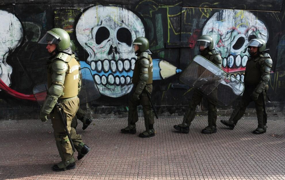 24. CHILE, Santiago, 14 lipca 2011: Policjanci pilnują dostępu do pałacu prezydenckiego podczas zamieszek z udziałem studentów. AFP PHOTO/CLAUDIO SANTANA