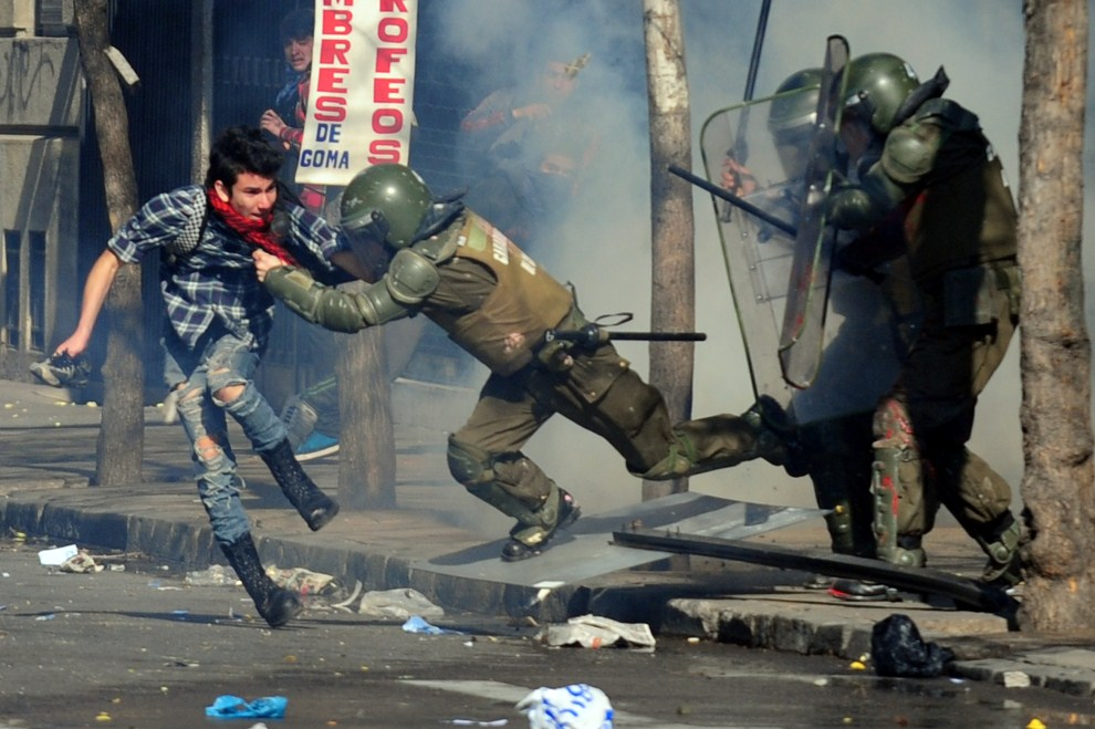 25. CHILE, Santiago, 14 lipca 2011: Policjant zatrzymuje studenta uczestniczącego w manifestacji przeciw prezydentowi i nowej ustawie o szkolnictwie. AFP PHOTO/CLAUDIO   SANTANA