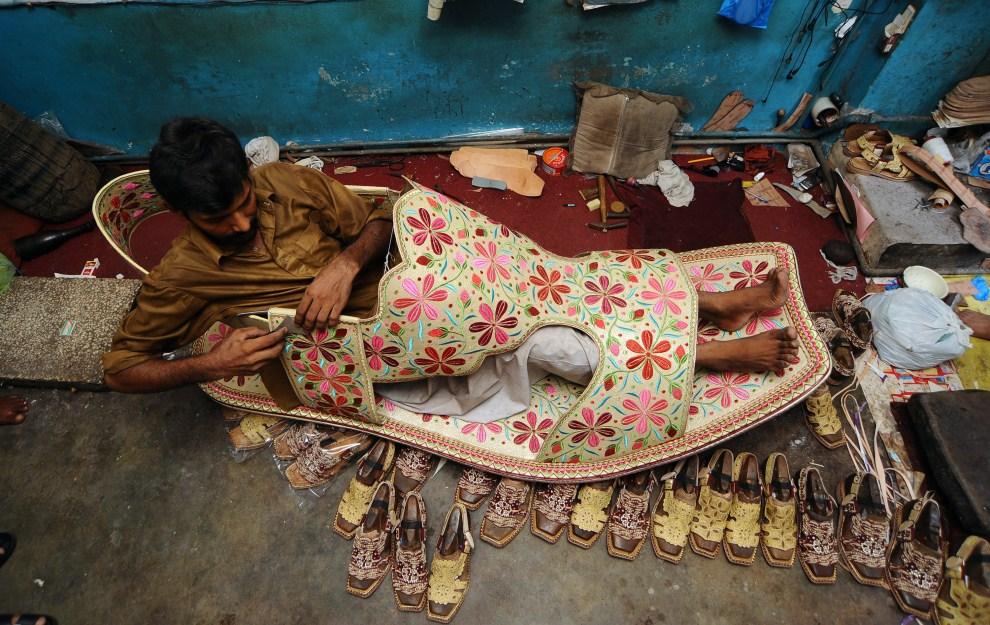 2. PAKISTAN, Lahore, 25 lipca 2011: Szewc o imieniu Hameed we wnętrzu blisko dwumetrowego buta, który będzie przyciągał klientów do jego zakładu w czasie święta Id al-Fitr.   AFP PHOTO/Arif ALI