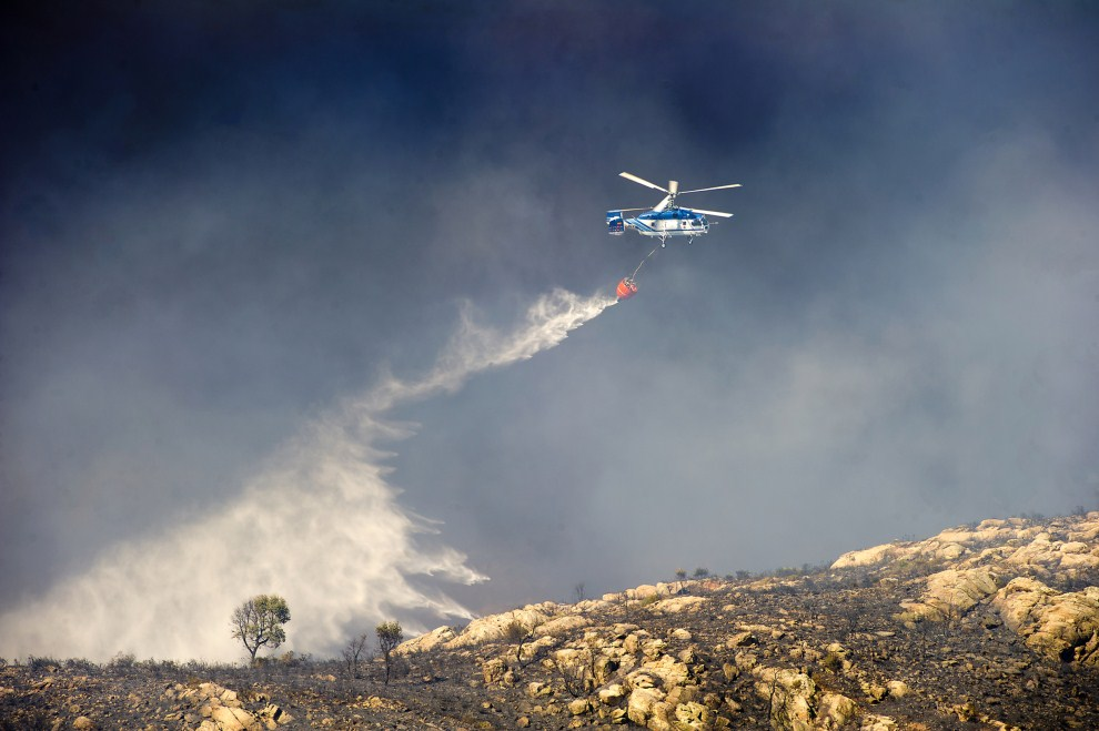 3. HISZPANIA, La Linea de la Concepción, 7 lipca 2011: Helikopter zrzuca wodę na płonące zbocze  Sierra Carbonera. AFP PHOTO / MARCOS MORENO