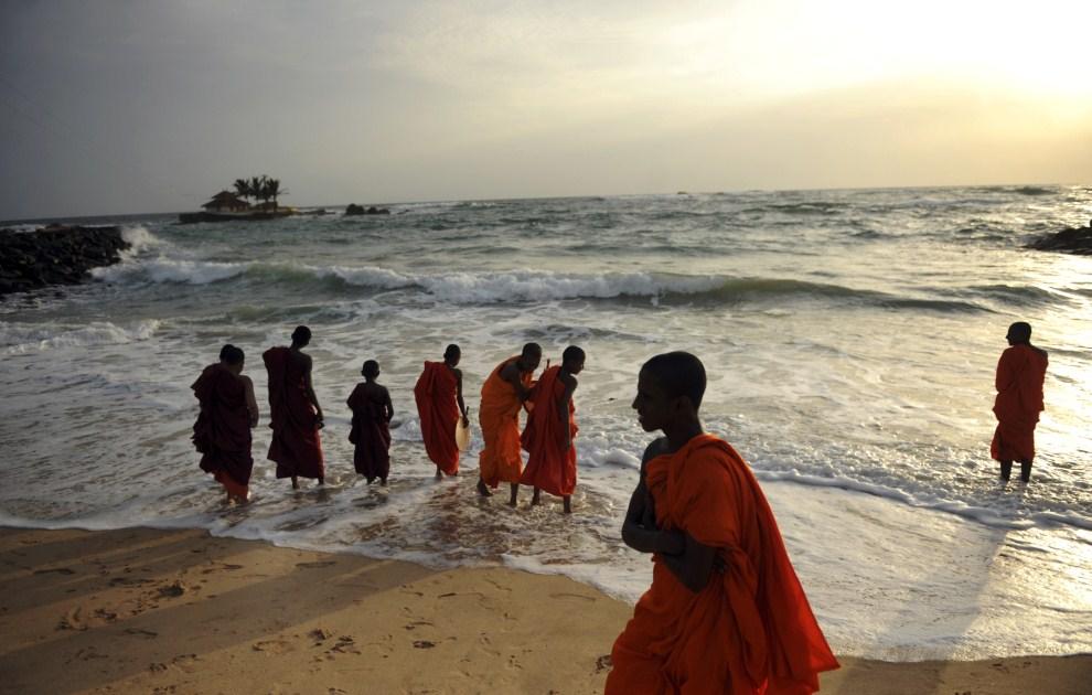 3. SRI LANKA, Seenigama, 21 lipca 2011: Mnisi przechadzający się plażą w pobliżu Seenigama. AFP PHOTO/Ishara S. KODIKARA.