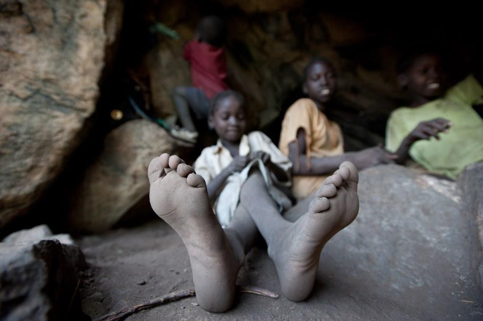 3. SUDAN, Lwere, 1 lipca 2011: Pięcioletnia Aisha Ahmed Ramadan ukrywa się w jaskini przed nalotami. AFP PHOTO/PHIL MOORE