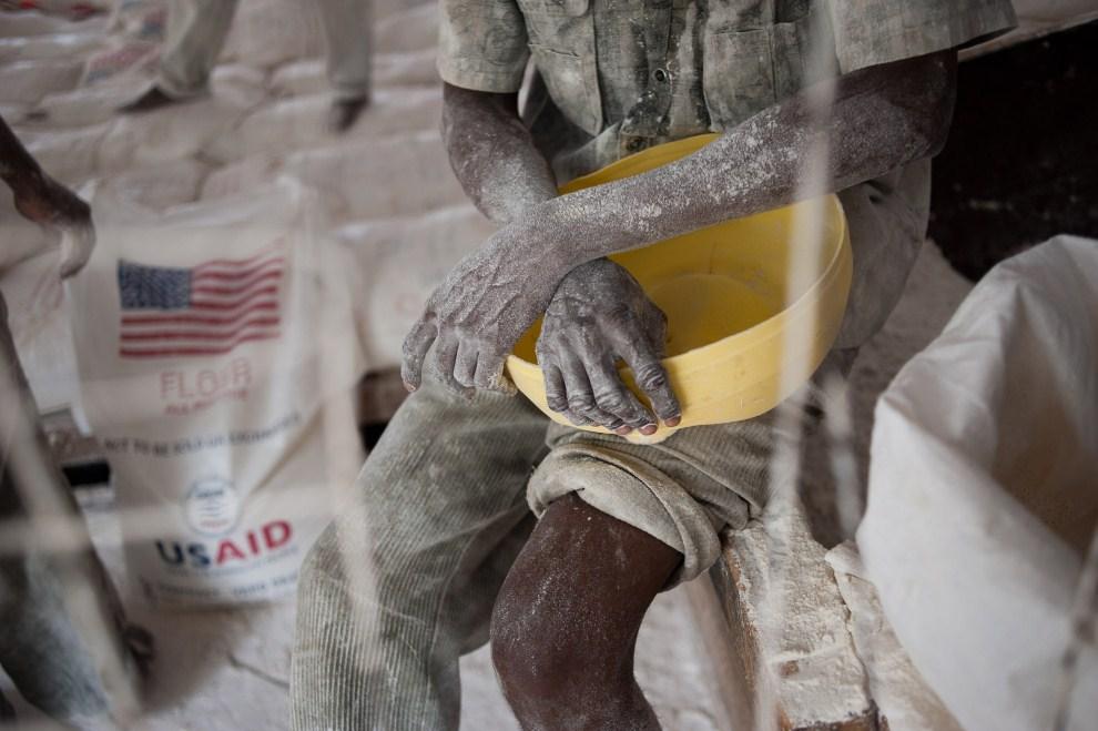 4. KENIA, Dadaab, 22 lipca 2011: Mężczyzna zatrudniony w punkcie dystrybucji mąki w obozie dla uchodźców. AFP PHOTO / PHIL MOORE