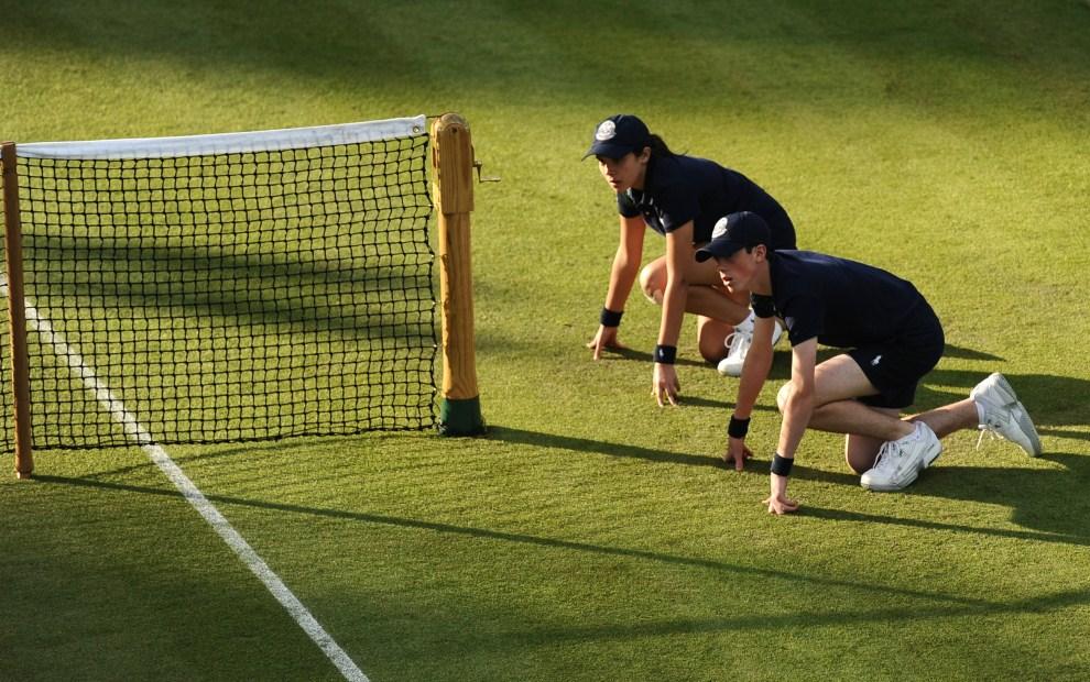 5. WIELKA BRYTANIA, Londyn, 21 czerwca 2011: Podający piłki czekają przy siatce na korcie. AFP PHOTO / CARL DE SOUZA