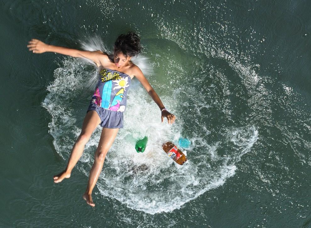 5. RUMUNIA, Bukareszt, 11 lipca 2011: Dziewczynka skacze do Dymbowicy w upalny, letni dzień. AFP PHOTO / DANIEL MIHAILESCU