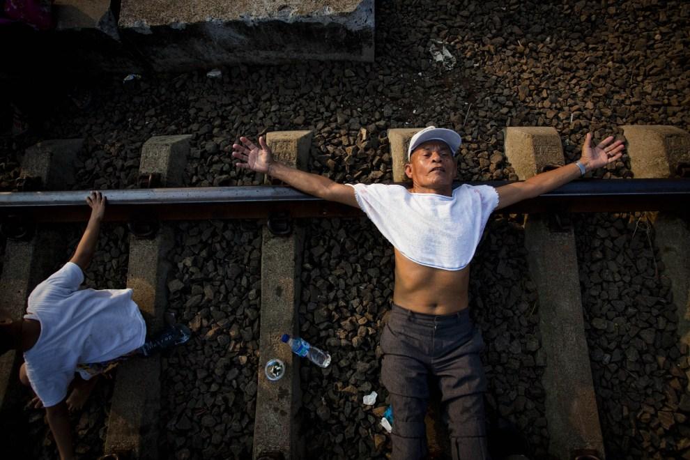 5. INDONEZJA, Dżakarta, 23 lipca 2011: Mężczyzna leży na torach w pobliżu stacji kolei elektrycznej. Mieszkańcy okolic wierzą, że płynący torami prąd leczy choroby i   pozwala cieszyć się zdrowiem. (Foto: Ulet Ifansasti/Getty Images)