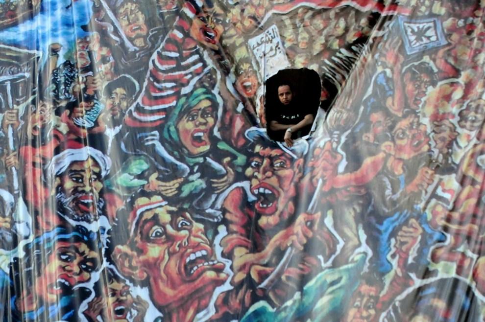 7. EGIPT, Kair, 18 lipca 2011: Mężczyzna obserwuje ludzi gromadzącym się na Placu Tahrir. AFP PHOTO/MOHAMED HOSSAM