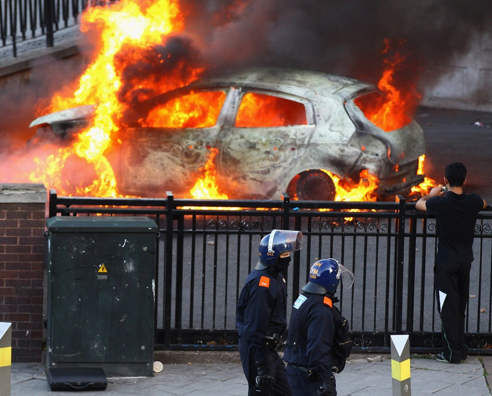 10. WIELKA BRYTANIA, Birmingham, 9 sierpnia 2011: Patrol policji mija podpalony samochód w centrum Birmingham. (Foto: Jeff J Mitchell/Getty Images)