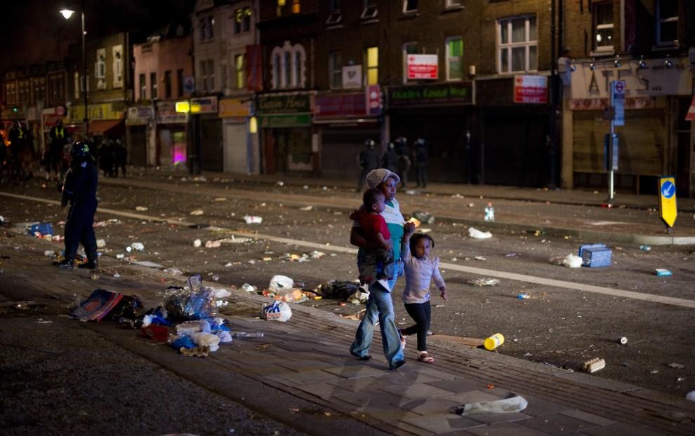 12. WIELKA BRYTANIA, Londyn, 6 sierpnia 2011: Kobieta z dziećmi na zdemolowanej ulicy w dzielnicy Tottenham. AFP PHOTO/LEON NEAL